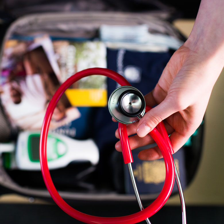 A student holds a stethoscope over a packed suitcase