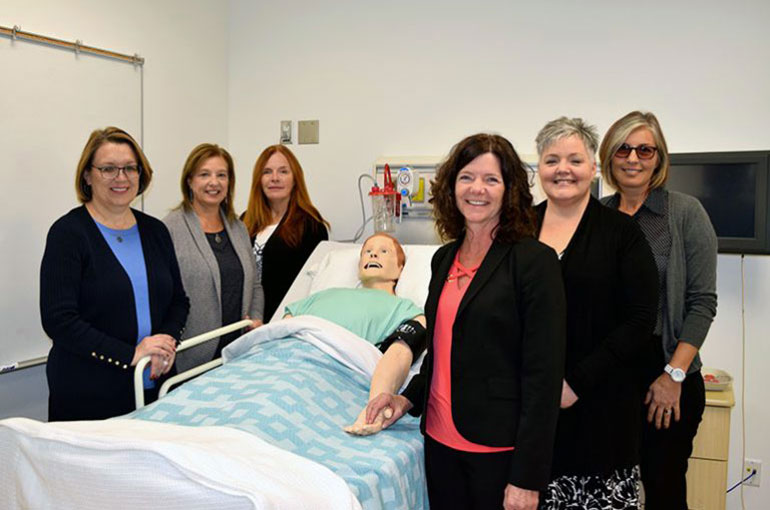 Six School of Nursing administrators and instructors standing around a simulation bed with a mannequin lying on it